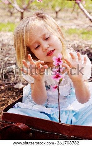 Cute girl wearing a blue dress sitting in vintage bag and playing with flowers  - stock photo