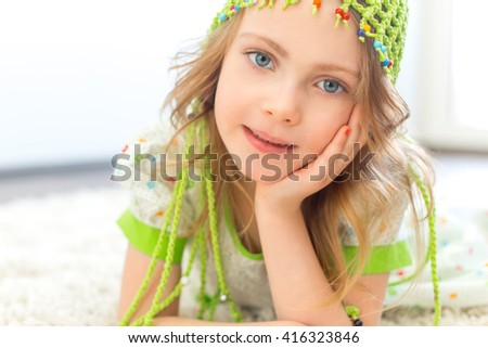Cute girl wearing a green hat on a furry white carpet - stock photo