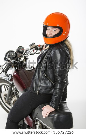 Cute girl with blond hair with orange motorcycle helmet. Studio shot on white background. Girl is sitting on a motorcycle. - stock photo