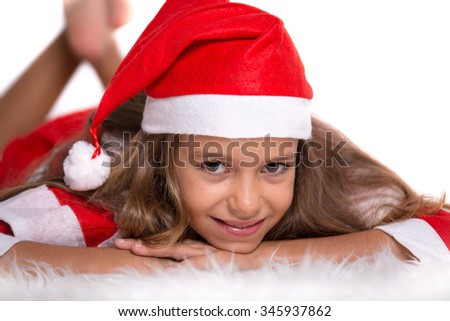 Cute girl with Christmas Santa hat and suit lying on a furry white carpet - stock photo