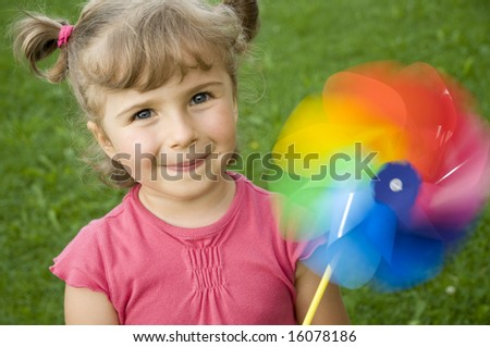 Cute girl with colored windmill toy - stock photo