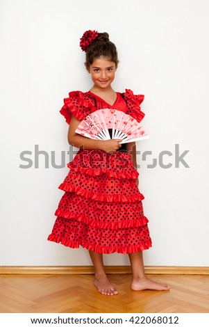 Cute girl with costume holding hand fan - stock photo