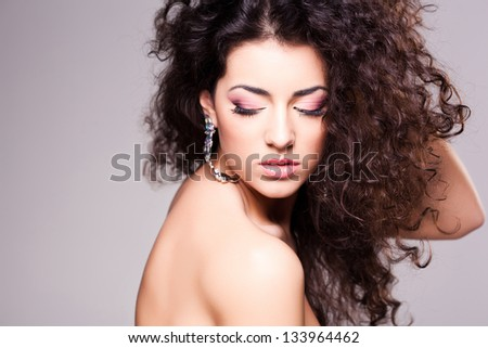 cute girl with curly hair wearing make-up - studio shot