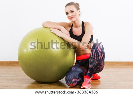Cute girl with dark hair wearing pink snickers, dark leggings and black short top sitting with fitball at gym, fitness, white wall and wooden floor. - stock photo