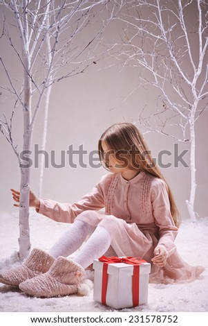 Cute girl with giftbox near by sitting in winter forest and touching bare tree trunk - stock photo