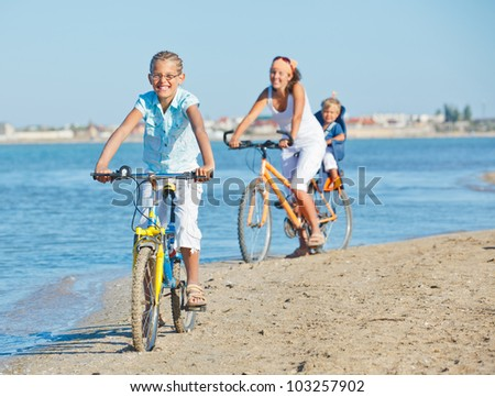 Cute girl with her mother and brother ride bikes along the beach. Focus on mother - stock photo
