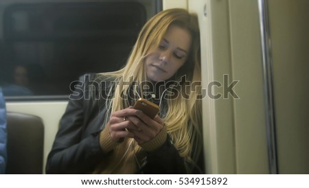 Cute girl with long blonde hair in leather jacket  straightens  use gadget in metro