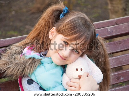 Cute girl with pigtails and a toy hare in hands