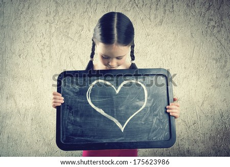 Cute girl with pigtails holds a board with a painted heart - stock photo