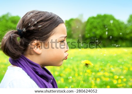 Cute girl with pigtails is blowing yellow Dandelion. Child playing outdoors. Girl is happy outside and having fun.