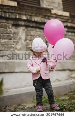 Cute girl with pink balloons urban portrait