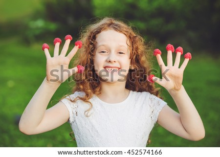 Cute girl with raspberries on her fingers showing her teeth. - stock photo