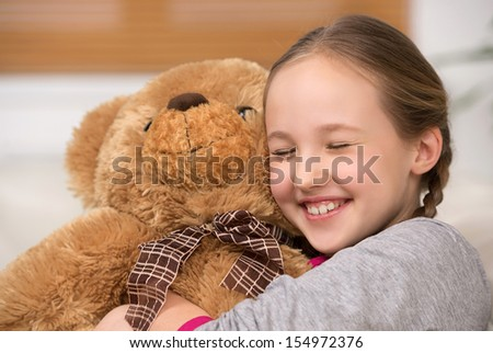 Cute girl with toy bear. Cheerful little girl hugging toy bear and smiling - stock photo