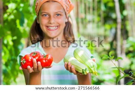 Cute girl with vegetables in summer garden. Focus on the  vegetables. - stock photo