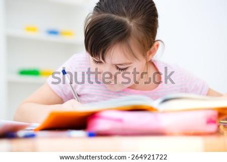 Cute girl writes a pen - concept school education - stock photo