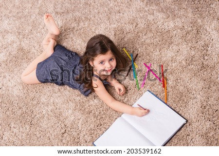 Cute girl writing letter on floor. nice girl drawing in notebook and smiling  - stock photo