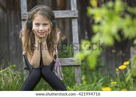 Cute girlie enjoys music with headphones on sitting in the courtyard of a village house. - stock photo