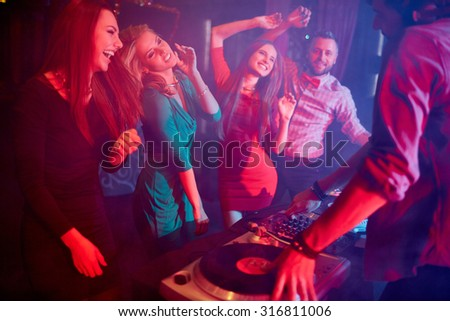 Cute girls dancing by turntables and dj adjusting sound - stock photo