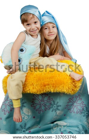 Cute girls in blue sleeping hats sitting with toy owl isolated on white - stock photo