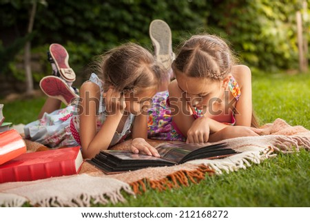 Cute girls lying on grass at park and looking at old family photos - stock photo