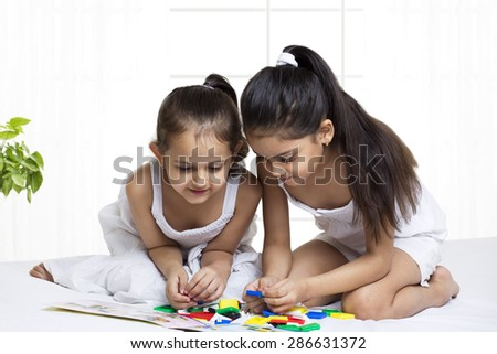 Cute girls solving puzzle
