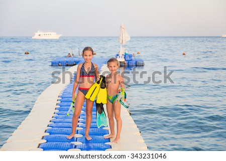 Cute girls with water masks and swim fins walking on pontoon