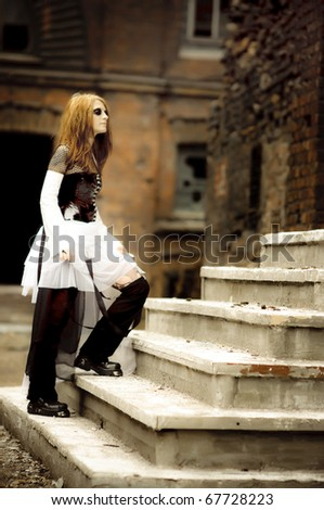 Cute gothic girl with face-art posing outdoors