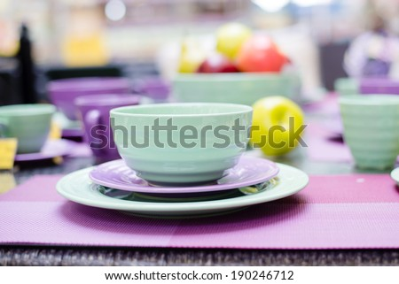 cute green and purple dinnerware sold in the supermarket shopping display shelf closeup image detail - stock photo