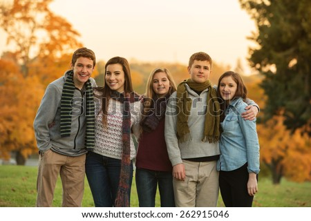 Cute group of teenage males and females in scarves outdoors - stock photo