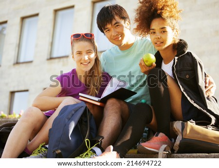 cute group of teenages at the building university with books huggings, back to school - stock photo
