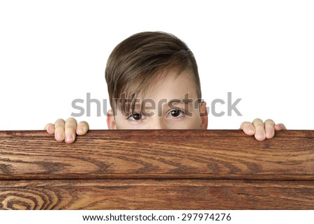 Cute handsome boy peeking from behind wooden fence isolated on white background - stock photo