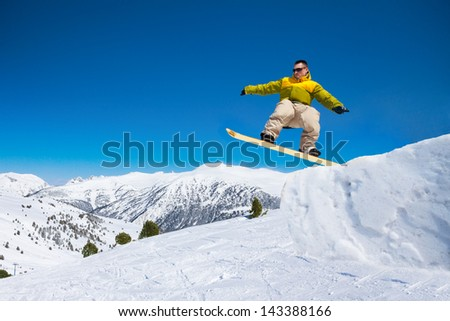 Cute handsome snowboard man in the air jumping in ski park