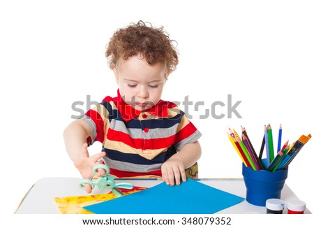 Cute happy baby boy kid child playing and cutting colorful paper with scissors isolated on white background studio portrait