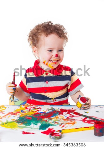 Cute happy baby boy kid child playing and painting with his face covered with spots of bright paints isolated on white background studio portrait - stock photo