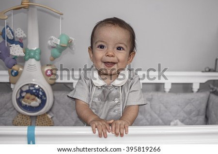 Cute happy baby, boy standing in wooden crib - stock photo