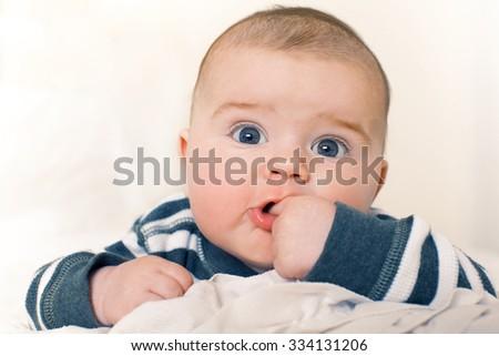 Cute happy baby boy with big blue eyes. - stock photo