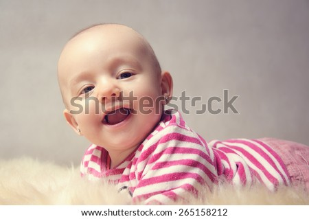 cute happy baby portrait lying on fur  - stock photo