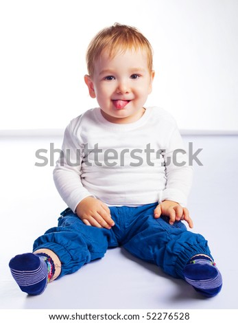cute happy baby sitting on the floor and showing tongue - stock photo