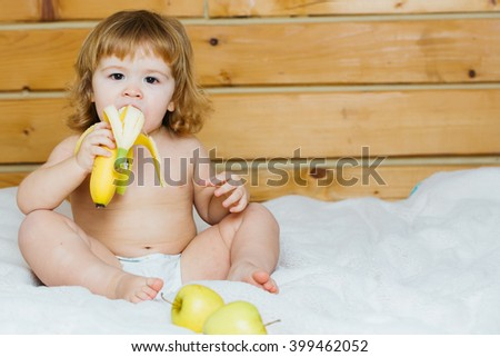 Cute happy beautiful smiling playful child boy with wet hair sitting in hothouse bath white fluffy towel naked indoor on wooden background eating banana and apple, horizontal picture - stock photo