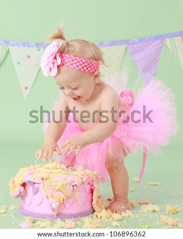Cute happy blond baby girl in pink tutu and flower head band standing on green background by smashed double tier heart decorated pink fondant iced cake with dirty sticky hands from messy crumb cake