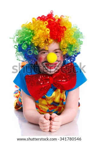 Cute happy boy clown lying on the floor over the white background - stock photo
