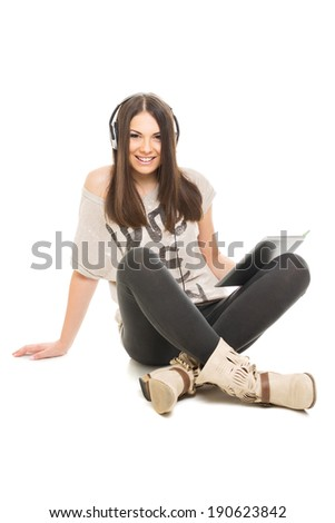 Cute happy brunet teenage girl with tablet listening music on headphones smiling sitting on the floor looking at camera isolated on white background. - stock photo