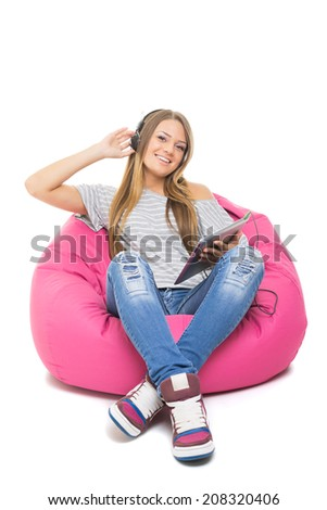 Cute happy Caucasian blonde teenage girl with headphones and tablet listening to music sitting on pink beanbag isolated on white background. - stock photo
