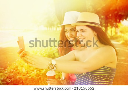 Cute happy Caucasian teenage girls taking a selfie in park. Two beautiful young women taking a self portrait photograph with smart phone outdoors in summer - stock photo