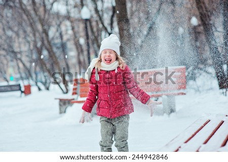 cute happy child girl in red coat and white hat throwing snow and laughing on the walk in winter park - stock photo