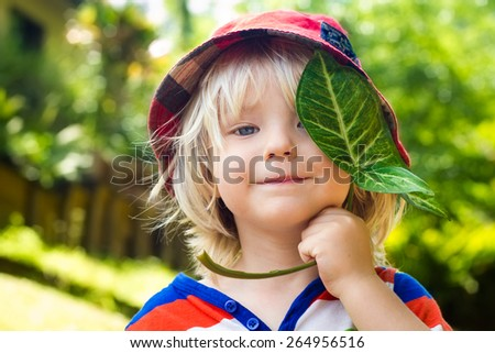 Cute happy child holding a leaf over his eye - stock photo