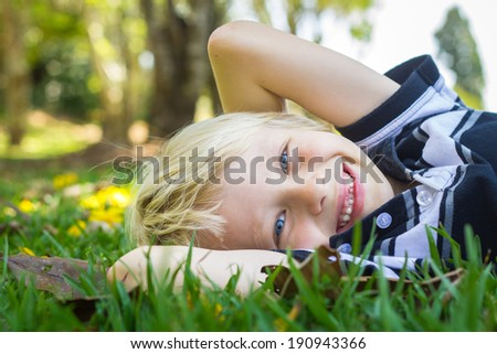 Cute happy child relaxing in park with arms behind his head on the grass - stock photo