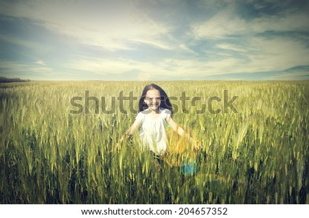 Cute happy child runs across the field of wheat - stock photo