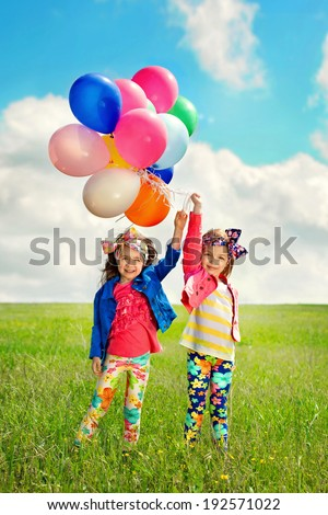 Cute happy children with balloons walking on spring field. Happiness, friendship, fashionable concept. - stock photo