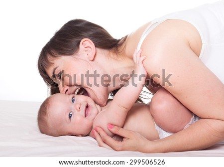 Cute happy family mother and baby on white background, mom biting kid's cheek - stock photo